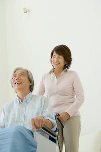 車いすに座る夫を支える妻の写真素材 [FYI04039670]