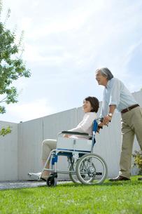 庭で車いすに座る妻を支える夫の写真素材 [FYI04039674]