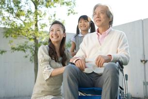 笑顔の車いすの祖父と母と娘の写真素材 [FYI04039690]