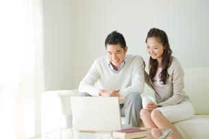ソファに座りパソコンをする夫婦の写真素材 [FYI04039698]