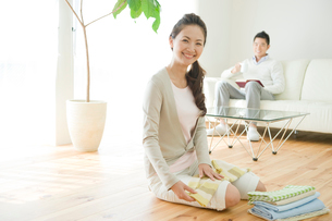 本を読む夫と洗濯物を畳む妻の写真素材 [FYI04039703]