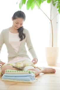洗濯物を畳む妻の写真素材 [FYI04039705]