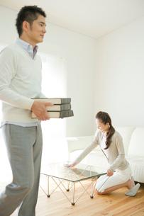 本を運ぶ夫とテーブルを拭く妻の写真素材 [FYI04039707]