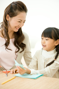 工作をする母と娘の写真素材 [FYI04039714]