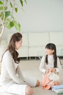 洗濯物を片付ける母と娘の写真素材 [FYI04039718]