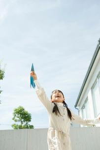 紙飛行機を飛ばす女の子の写真素材 [FYI04039720]