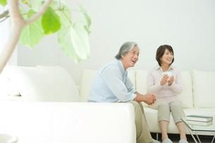 リビングで話す老夫婦の写真素材 [FYI04039721]