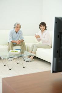 リビングでテレビを見る老夫婦の写真素材 [FYI04039729]