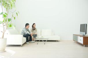 リビングでテレビを見る夫婦の写真素材 [FYI04039730]