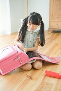 ランドセルに教科書を詰める女の子の写真素材 [FYI04039741]