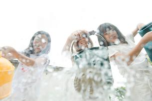 ジョウロで遊ぶ3人の女の子の写真素材 [FYI04039774]