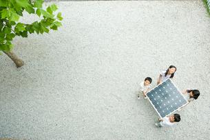 ソーラーパネルを持つ2人の男の子と2人の女の子の写真素材 [FYI04039780]