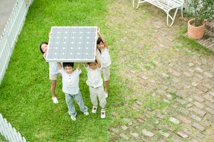 ソーラーパネルを持上げる2人の男の子と2人の女の子の写真素材 [FYI04039783]