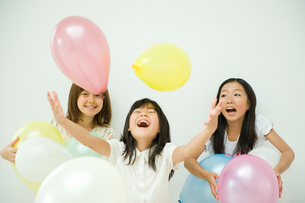風船で遊ぶ3人の女の子の写真素材 [FYI04039809]
