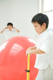 風船を膨らませる男の子と耳をふさぐ男の子の写真素材 [FYI04039811]