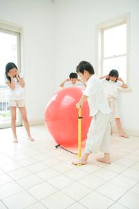 風船を膨らませて遊ぶ2人の男の子と2人の女の子の写真素材 [FYI04039812]