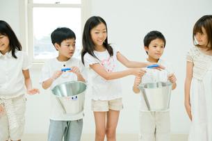 バケツリレーをする2人の男の子と3人の女の子の写真素材 [FYI04039813]
