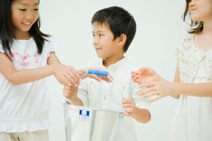 バケツリレーをする男の子と2人の女の子の写真素材 [FYI04039814]