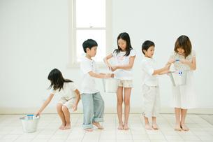 バケツリレーをする2人の男の子と3人の女の子の写真素材 [FYI04039815]
