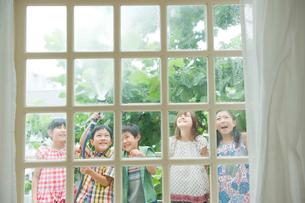 窓の外で水を撒いて遊ぶ2人の男の子と3人の女の子の写真素材 [FYI04039819]