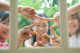 窓ガラスに指を当てて遊ぶ3人の女の子の写真素材 [FYI04039822]