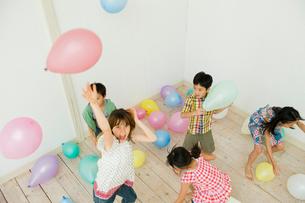 風船で遊ぶ2人の男の子と3人の女の子の写真素材 [FYI04039836]
