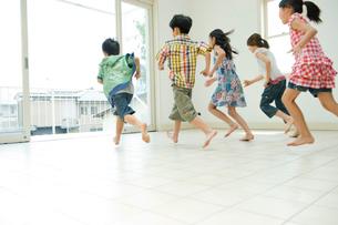 家の中から外に走る2人の男の子と3人の女の子の写真素材 [FYI04039837]