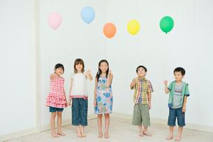 風船を持って立つ2人の男の子と3人の女の子の写真素材 [FYI04039845]