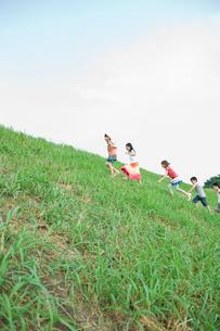 坂の草むらを上る2人の男の子と3人の女の子の写真素材 [FYI04039849]