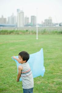 ビニール袋に空気を入れる男の子の写真素材 [FYI04039860]