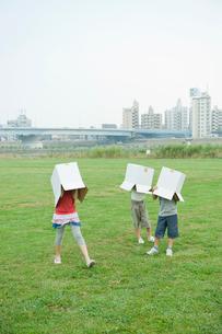 ダンボール箱を被る女の子と2人の男の子の写真素材 [FYI04039861]
