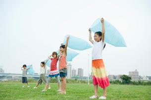 ビニール袋に空気を入れる2人の男の子と3人の女の子の写真素材 [FYI04039864]