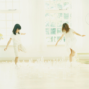 ペットボトルの間を歩く2人の女の子の写真素材 [FYI04039873]