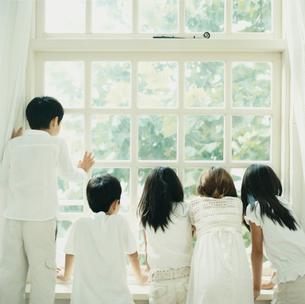窓から外を見る3人の女の子と2人の男の子の写真素材 [FYI04039881]