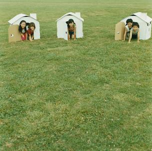 紙の家から身体を出す3人の女の子と2人の男の子の写真素材 [FYI04039897]