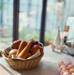 窓際に置かれたかごに入った野菜や果物の写真素材 [FYI04039951]