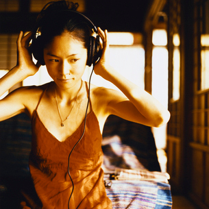ヘッドホンで音楽を聴く日本人女性の写真素材 [FYI04040038]