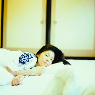 布団に横になる浴衣姿の20代日本人女性の写真素材 [FYI04040058]