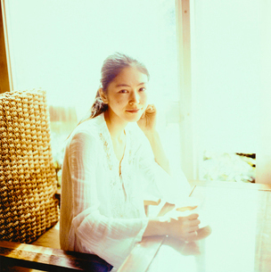 コーヒーカップを手に座る20代日本人女性の写真素材 [FYI04040079]