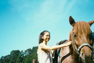 馬をなでる20代日本人女性の写真素材 [FYI04040082]