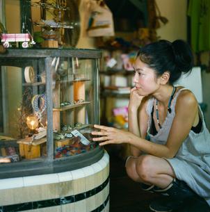 雑貨屋のショーケースをのぞく20代日本人女性の写真素材 [FYI04040097]