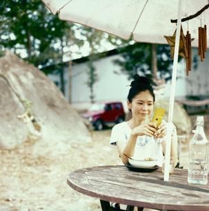 外で食事をしながらメールする20代日本人女性の写真素材 [FYI04040099]