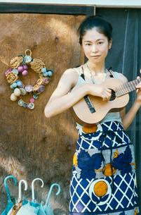 ドアの前でギターを弾く20代日本人女性の写真素材 [FYI04040101]