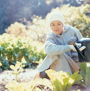 畑の野菜に水をやろうとする日本人女性の写真素材 [FYI04040119]