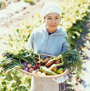 畑で収穫した野菜を抱える日本人女性の写真素材 [FYI04040122]