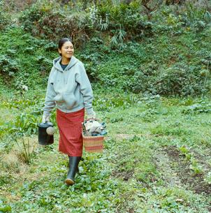 ジョーロと籠を手に畑の中を歩く日本人女性の写真素材 [FYI04040129]