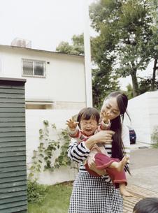 庭で泣く幼児をあやす日本人の母の写真素材 [FYI04040148]