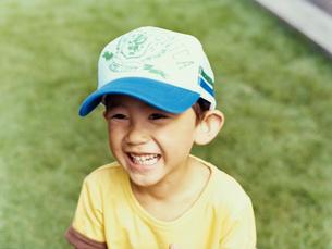 庭で笑うキャップを被った日本人男児の写真素材 [FYI04040184]