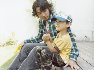 ウッドデッキに座る父とキャップを被った男児の写真素材 [FYI04040187]