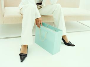 ソファに座るキャリアウーマンの足元と紙袋の写真素材 [FYI04040232]